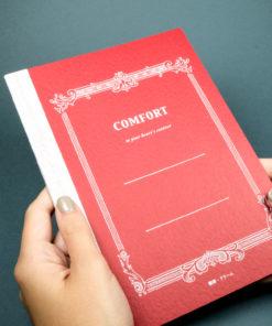 Life Comfort Notebook held on Dark Background